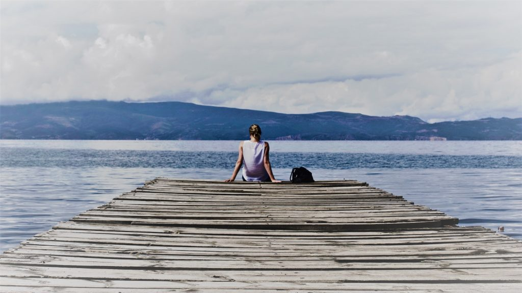 Woman sitting on a pier looking out across a lake towards hills.