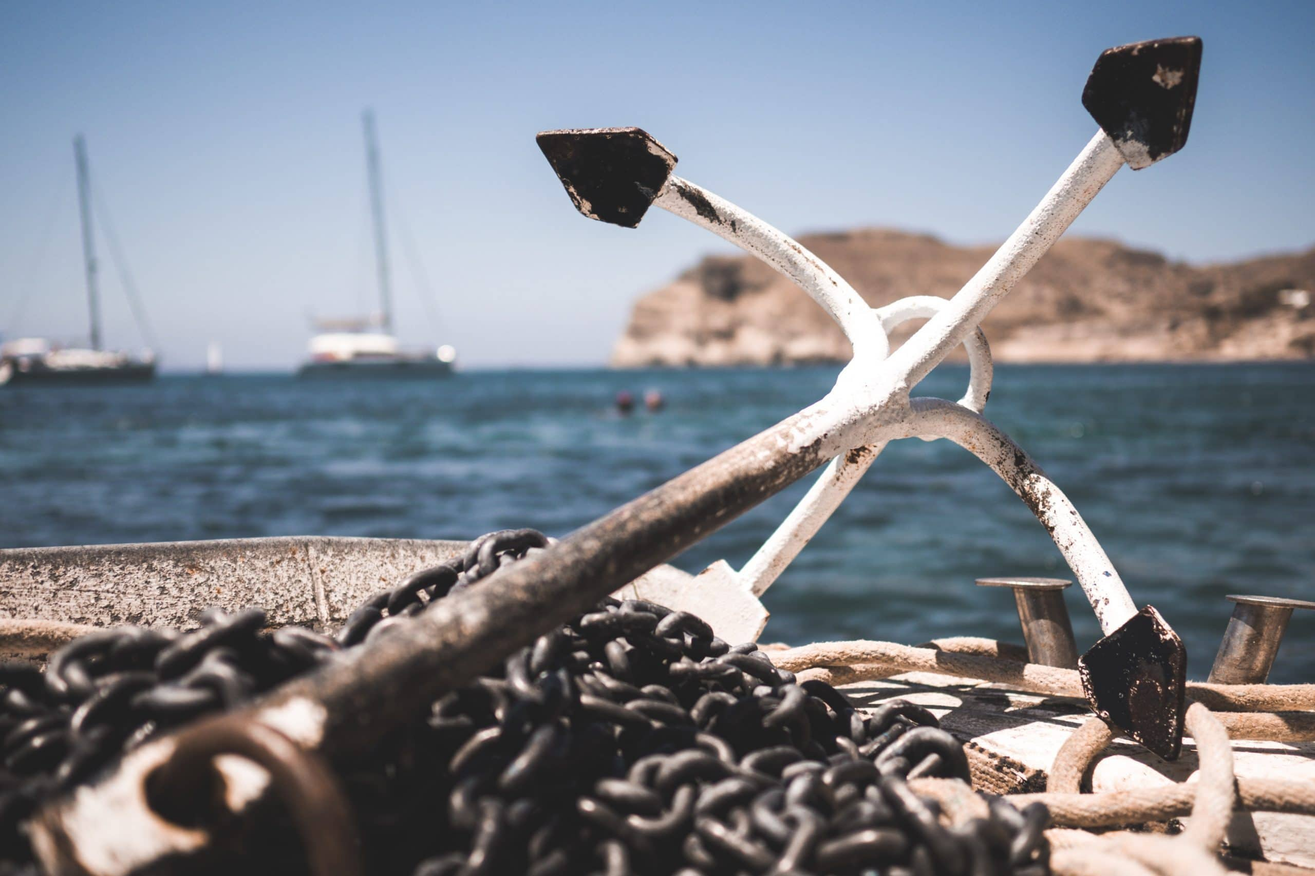 Real anchor and chains on a deck by the sea