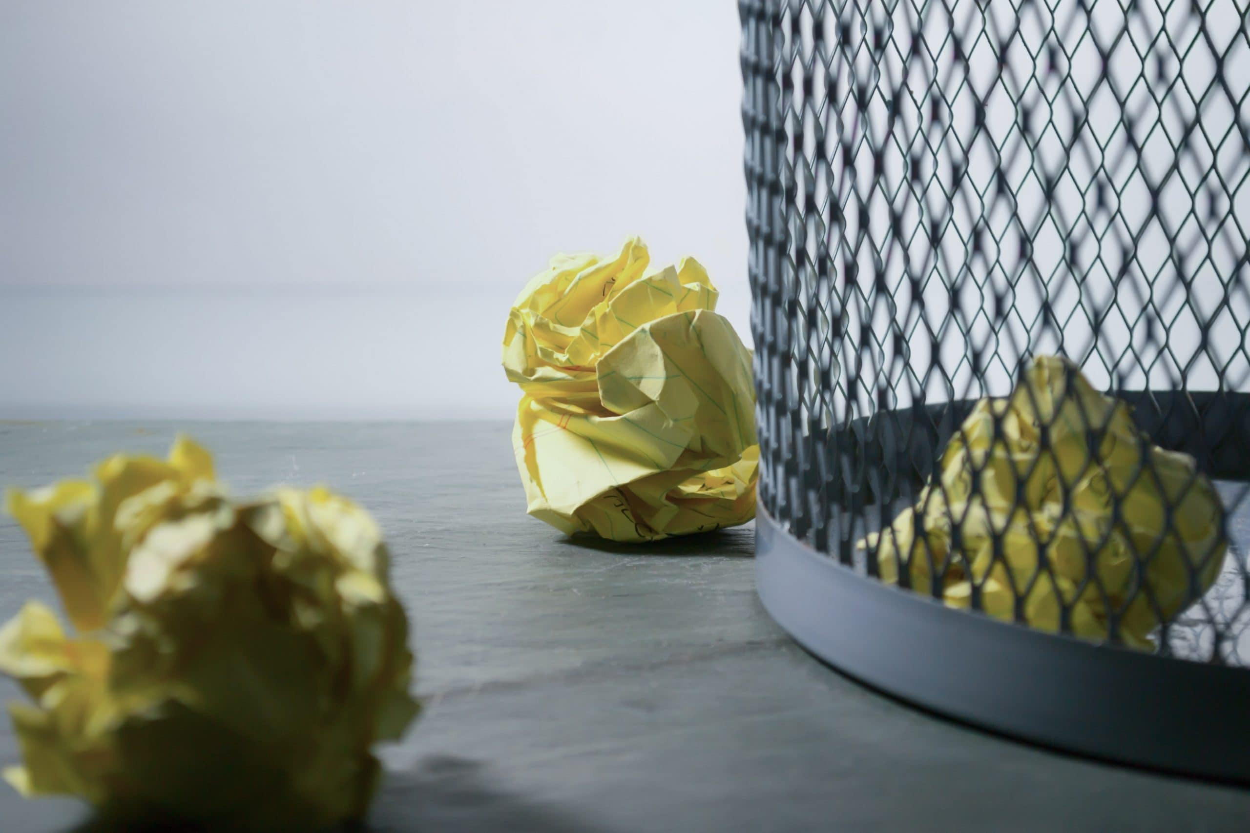 Bin with several pieces of scrunched up yellow paper in it and near it