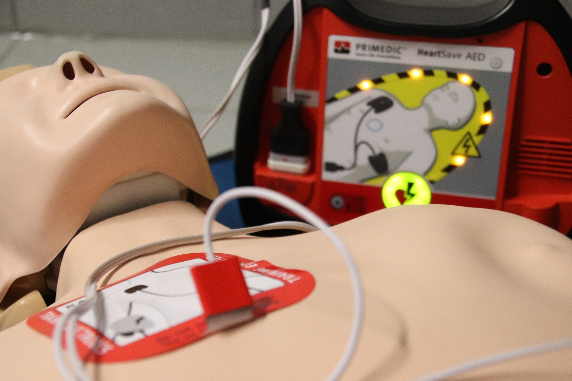 Resuscitation dummy next to a defibrillator - one of the defibrillator pads is on the dummy's chest.