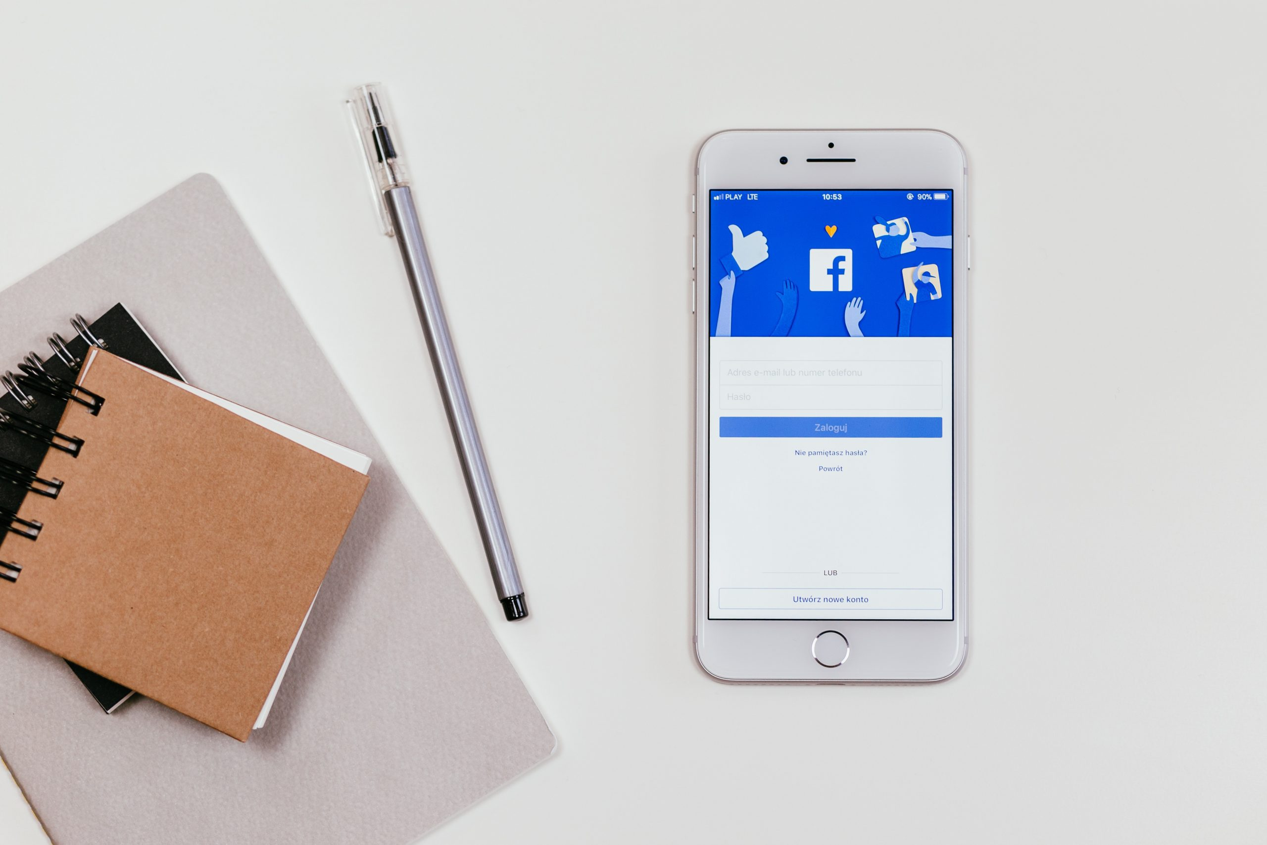 Facebook on the screen of a mobile phone next to a pen and some notebooks