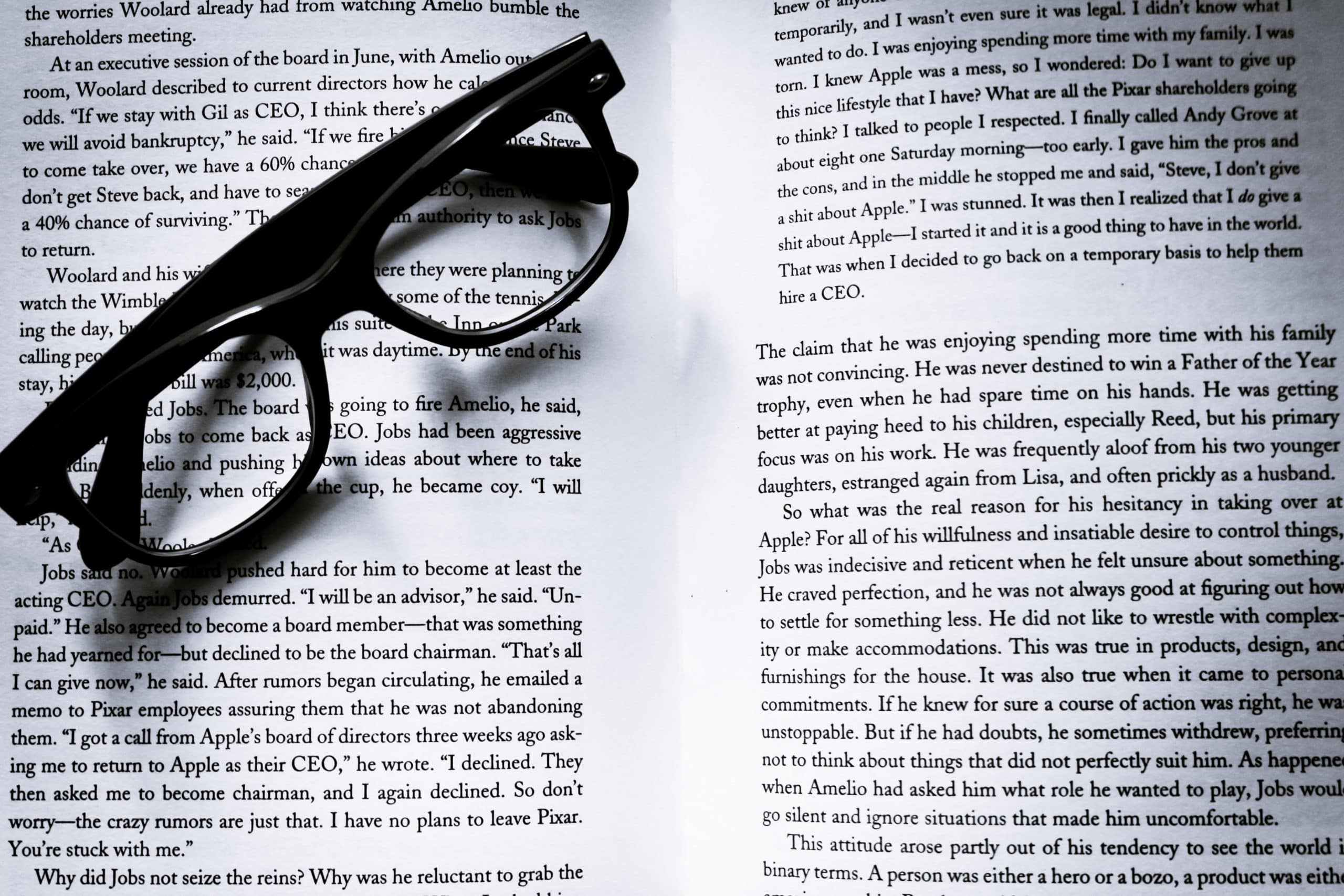 Text in an open book, with glasses on top