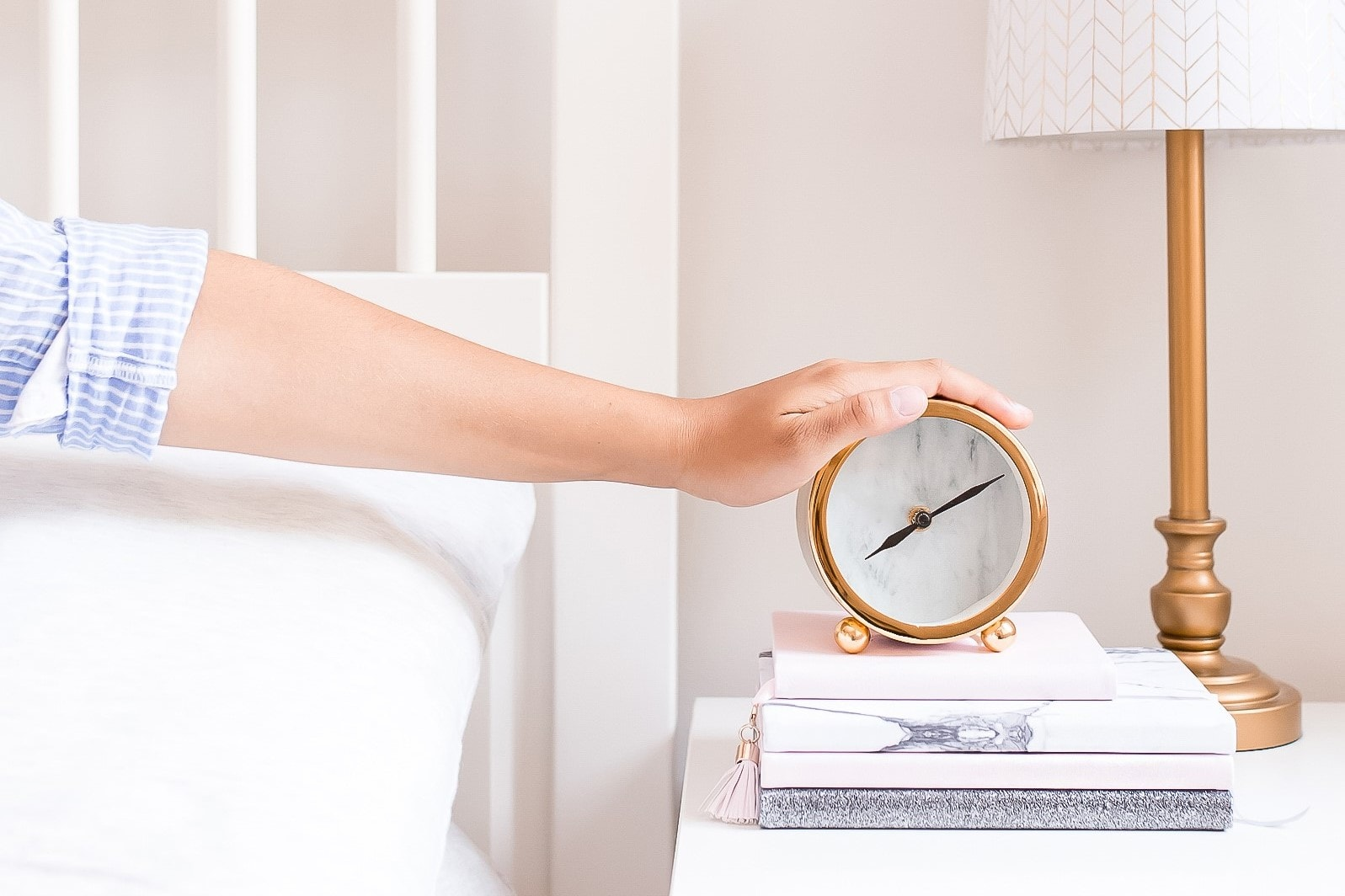 Woman in bed with her hand on her alarm clock