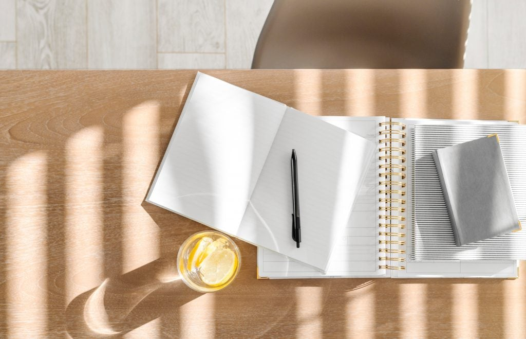 Notebooks, pen and glass of water on a desk