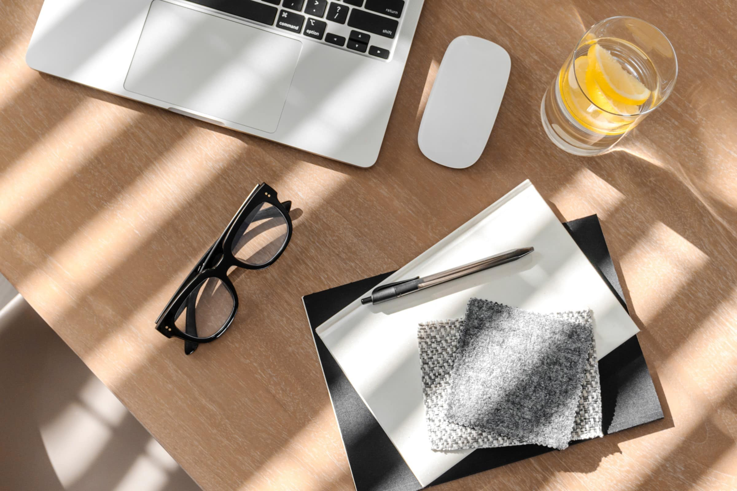 Notepads, laptop, mouse, glasses and glass of water on a desk
