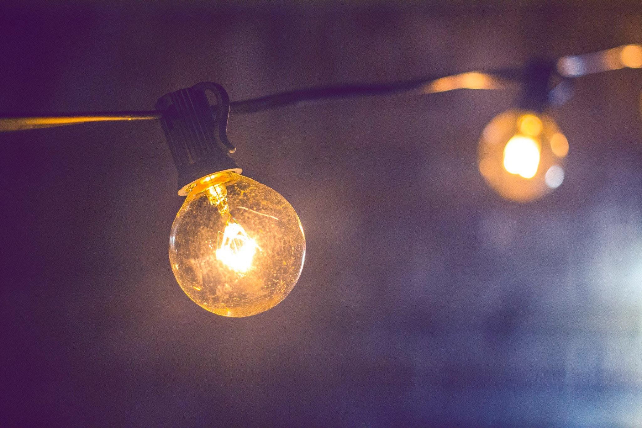 Two bare lightbulbs glowing in the dark