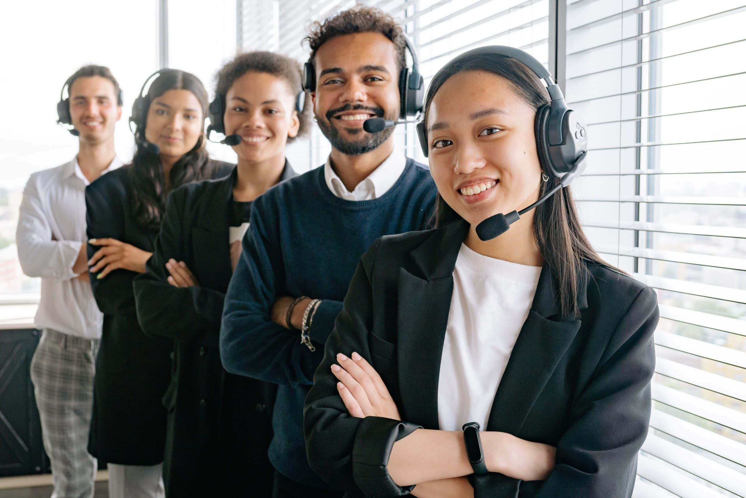 5 Customer Service people standing in a row with headsets on