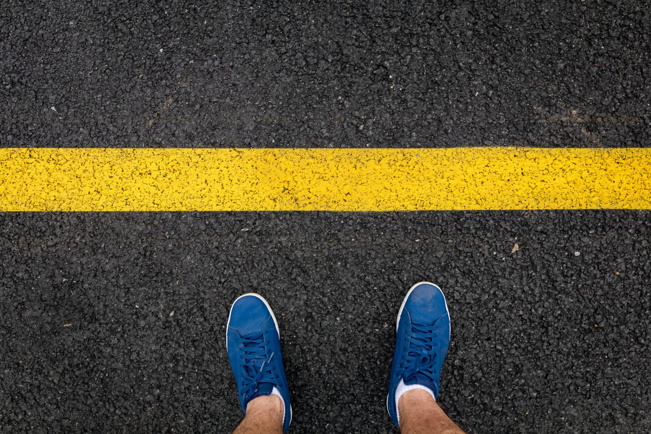 Overhead of someone's feet standing in front of a big yellow line painted onto the road